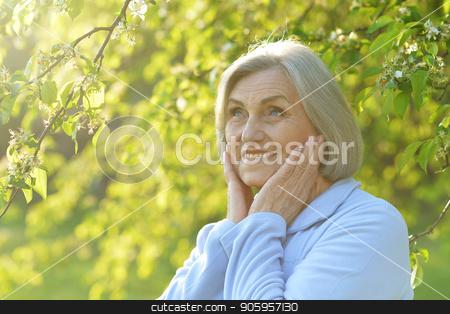 Senior woman in green park stock photo, Portrait of a beautiful senior woman in green park by Ruslan Huzau