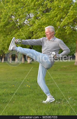 Elderly man exercising with dumbbells stock photo, Elderly man exercising with dumbbell in  park by Ruslan Huzau