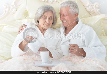 Senior couple in bed with tea stock photo, happy Senior couple in white bathrobes drinking tea in bed by Ruslan Huzau