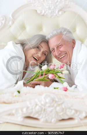 senior man gives flowers to a woman stock photo, happy senior couple with flowers lying in bed by Ruslan Huzau