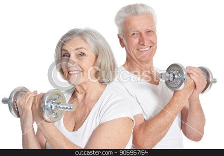 smiling senior couple exercising stock photo, Active smiling senior couple exercising isolated on white by Ruslan Huzau