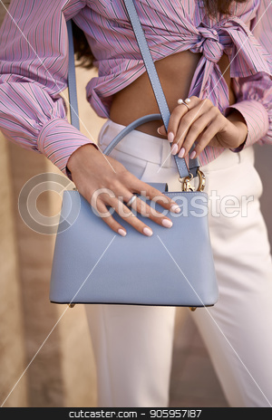 Model with bag outdoors stock photo, Pretty girl is posing with a light blue bag on the wall background outdoors. She wears a white pants and a colorful striped shirt. Closeup vertical photo. by bezikus