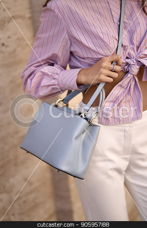 Model with bag outdoors stock photo, Cute girl is posing with a light blue bag on the wall background outdoors. She wears a white pants and a colorful striped shirt. Closeup vertical photo. by bezikus