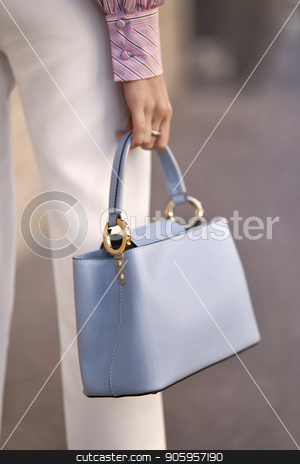 Model with bag outdoors stock photo, Attractive girl is posing with a light blue bag outdoors. She wears a white pants and a colorful striped shirt. Closeup vertical photo. by bezikus
