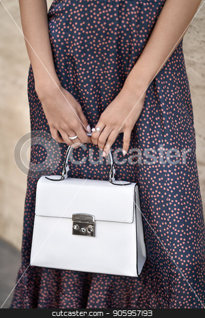Model with bag outdoors stock photo, Gorgeous girl is posing with a white bag on the wall background outdoors. She wears a colorful dotted dress. Closeup vertical photo. by bezikus