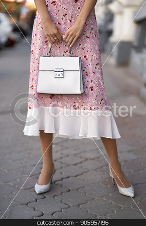 Model with bag outdoors stock photo, Charming girl is posing with a white bag on the street background outdoors. She wears a pink dress with flower prints and light shoes. Closeup vertical photo. by bezikus