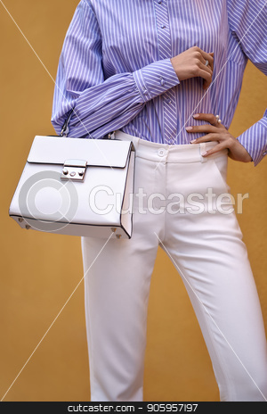 Model with bag outdoors stock photo, Slim girl is posing with a white bag on the yellow wall background outdoors. She wears a white pants and a colorful striped shirt. Closeup vertical photo. by bezikus