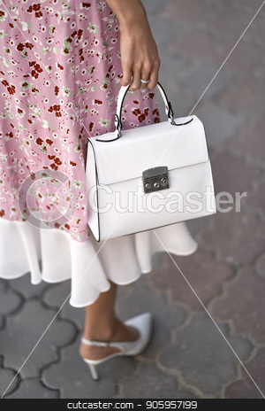 Model with bag outdoors stock photo, Girl is posing with a white bag on the street background outdoors. She wears a pink dress with flower prints and light shoes. Closeup vertical photo. by bezikus