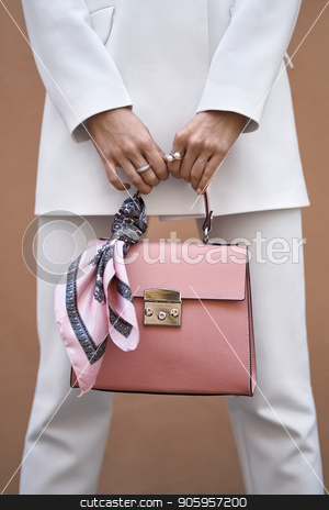 Model with bag outdoors stock photo, Woman is posing with a coral bag with a pink silk scarf on the wall background outdoors. She wears a white pantsuit. Closeup vertical photo. by bezikus