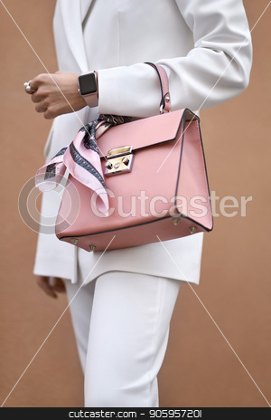 Girl with bag outdoors stock photo, Model is posing with a coral bag with a pink silk scarf on the wall background outdoors. She wears a white pantsuit. Closeup vertical photo. by bezikus