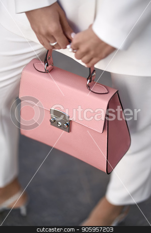 Model with bag outdoors stock photo, Nice girl is posing with a coral bag on the wall background outdoors. She wears a white pantsuit with light shoes. Closeup vertical photo. by bezikus