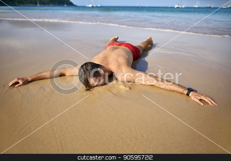 Tanned guy on beach stock photo, Pretty tanned man lies with outstretched arms on the sand beach on the sunny background of the sea with white boats and the blue sky. He wears a red swim trunks and a dark watch. Horizontal. by bezikus