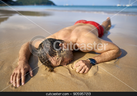 Tanned guy on beach stock photo, Cute tanned man with closed eyes lies on the stomach on the sand beach on the sunny background of the sea with white boats and the blue sky. He wears a red swim trunks and a dark watch. Horizontal. by bezikus