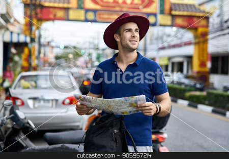 Traveler on city street stock photo, Joyful tourist with a map in the hands stands on the city street and looks to the side. He wears a blue polo, gray shorts, crimson hat and a black backpack. Outdoors. Horizontal. by bezikus