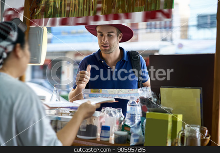 Traveler on city street stock photo, Tourist with a map in the hands asks a question to local seller on the city street background. He wears a blue polo, crimson hat and a black backpack. Outdoors. Horizontal. by bezikus