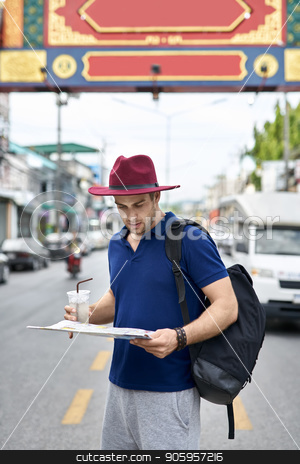 Traveler on city street stock photo, Thoughtful tourist with a map in the hands stands on the city street. He wears a blue polo, gray shorts, crimson hat, black backpack and holds also a drink. Outdoors. Vertical. by bezikus