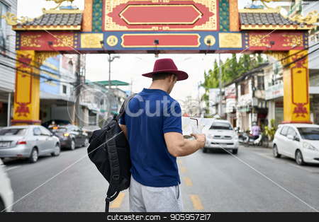 Traveler on city street stock photo, Young tourist with a map in the hands stands on the city street. He wears a blue polo, gray shorts, crimson hat, black backpack and holds also a drink. Outdoors. Shoot from the back. Horizontal. by bezikus