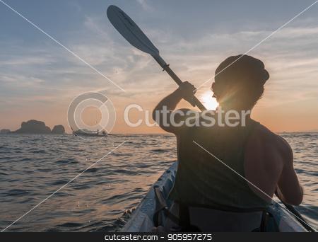 Kayaking. Man With kayak paddle at sunset sea Rowing to the Sun. stock photo, Kayaking. Man in cap With kayak paddle at sunset sea Rowing to the Sun. by Gideon Ikigai