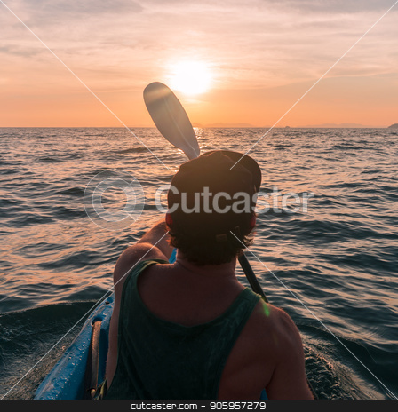 Kayaking. Man With kayak paddle at sunset sea Rowing to the Sun. stock photo, Kayaking. Man in cap With kayak paddle at sunset sea Rowing to the Sun. by Gideon Ikigai