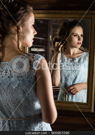 young elegant woman in front of mirror, gold and wood stock photo, young elegant woman in front of mirror, gold and wood. by Alexander