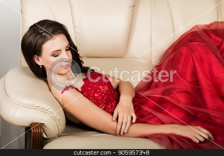 young elegant woman with professional hairstyle in long red dress rested on sofa stock photo, young elegant woman with professional hairstyle in long red dress rested on sofa. by Alexander