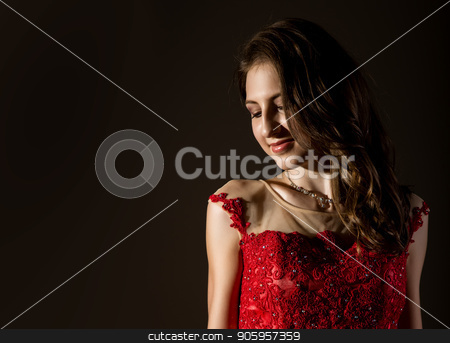 Shy woman lowered her eyes smiles timid. Girl in elegant red dress on a dark background. free space for your text stock photo, Shy woman lowered her eyes smiles timid. Girl in elegant red dress on a dark background by Alexander