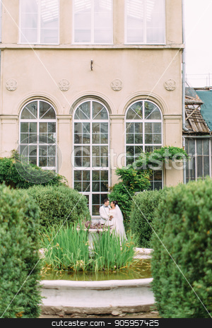 Full-length view of the newlyweds standing near the old building in the garden. stock photo, Full-length view of the newlyweds standing near the old building in the garden by Andrii Kobryn