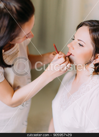 The vertical view of the womanmakeup artist doing the makeup for the bride stock photo, The vertical view of the womanmakeup artist doing the makeup for the bride. by Andrii Kobryn