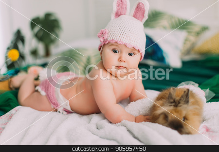 The side portrait of the baby with the knitted pink hat with rabbit ears lying near the bunny on the bed. stock photo, The side portrait of the baby with the knitted pink hat with rabbit ears lying near the bunny on the bed. by Andrii Kobryn