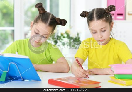 two sisters twins stock photo, Cute twin sisters doing homework at their room by Ruslan Huzau