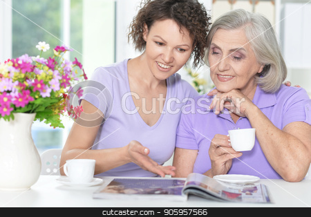 Senior woman with daughter stock photo, Portrait of Senior woman with daughter reading magazine at home by Ruslan Huzau