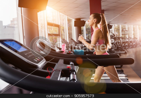 pretty girl running at the treadmill stock photo, slim pretty girl running at the treadmill in the gym against the sunset. Concept of cardio exercises and healthy way of life by Oleh