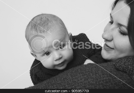 Son peeks over the shoulder of the mother. A woman in a sweater holding a child stock photo, Son peeks over the shoulder of the mother. A woman in a sweater holding a child by aaalll3110