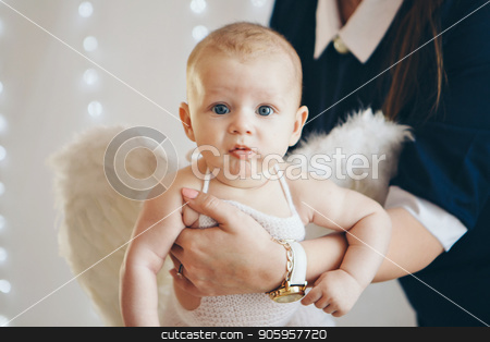a small child with wings of an angel lying on women's hands. stock photo, a small child with wings of an angel lying on women's hands. by aaalll3110