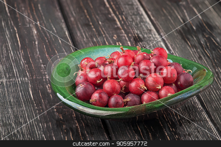 Red gooseberry in clay bowl stock photo, Red gooseberry in clay bowl. Wooden table. Blurred background. by Vitalii Borovyk
