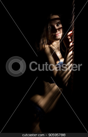 Beautiful woman in underwear stending near window and closed louver on a sunny day. Striped shadow on a body stock photo, Beautiful woman in underwear stending near window and closed louver on a sunny day. Striped shadow on a body. by Alexander