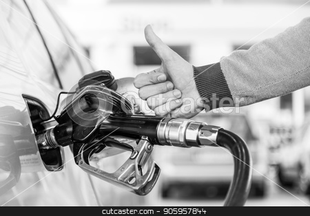 Petrol or gasoline being pumped into a motor vehicle car. Closeup of man, showing thumb up gesture, pumping gasoline fuel in car at gas station. stock photo, Petrol or gasoline being pumped into a motor vehicle car. Closeup of mans hand showing thumb up gesture, pumping gasoline fuel in car at gas station. Black and white image. by kasto