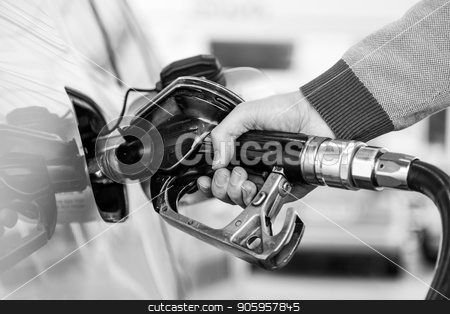 Closeup of mans hand pumping gasoline fuel in car at gas station. stock photo, Pumping gas at gas pump. Closeup of man pumping gasoline fuel in car at gas station. Black and white image. by kasto