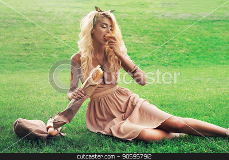 Beauty blonde alone young woman resting in the park stock photo, Rest in park, outdoor, people and food concept - beauty blonde young woman eating in the park by olinchuk