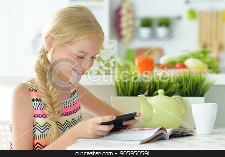 the girl in the kitchen stock photo, girl with the phone in the kitchen by Ruslan Huzau