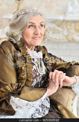 senior woman sitting in vintage chair stock photo, Beautiful senior woman in dress sitting in vintage chair near fireplace by Ruslan Huzau