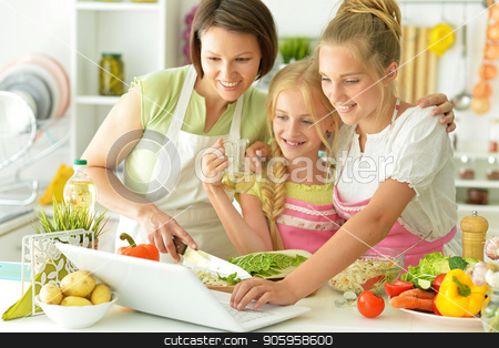mother and two daughters stock photo, mother and two daughters in the kitchen by Ruslan Huzau