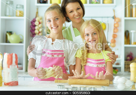 sisters and mom in the kitchen stock photo, sisters and mother in the kitchen preparing by Ruslan Huzau