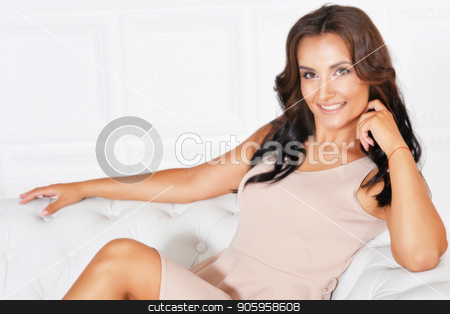 portrait of beautiful woman in dress stock photo, portrait of beautiful woman in dress  posing on sofa by Ruslan Huzau