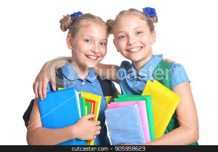 Cute schoolgirls with backpacks stock photo, Cute schoolgirls with backpacks and books posing isolated on white background by Ruslan Huzau
