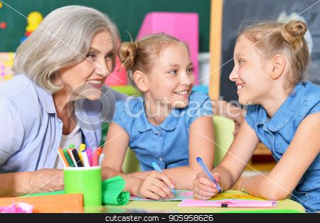 Grandmother with two adorable twin granddaughters stock photo, Grandmother with two adorable twin granddaughters drawing together by Ruslan Huzau
