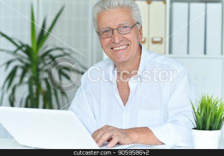 senior man using laptop stock photo, Portrait of senior man using laptop at home by Ruslan Huzau