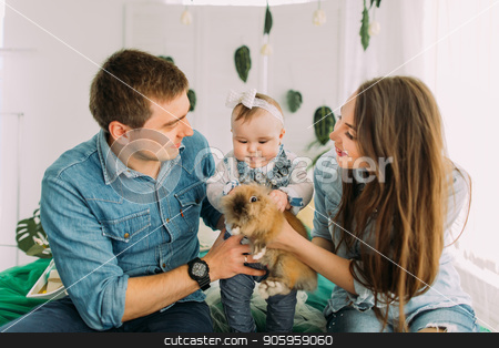 Cheerful family is playing with the little baby. The baby is petting the rabbit. stock photo, Cheerful family is playing with the little baby. The baby is petting the rabbit by Andrii Kobryn