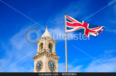 Clock and British Flag stock photo, An old stone clock tower and British flag against a cloudy sky by Darryl Brooks