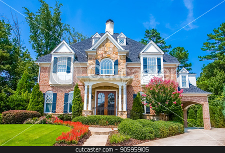 Brick and Stone House with Flowers stock photo, A nice brick and stone house with many flowers in front by Darryl Brooks